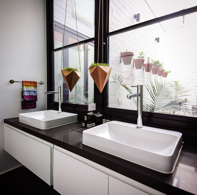In this black and white bathroom, there's windows providing lots of natural light and views of a small courtyard.