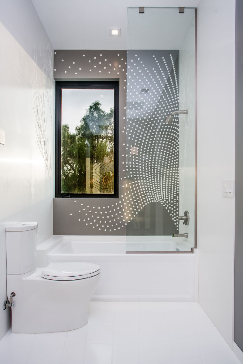 This modern bathroom has artistic tile pattern covering the wall in the shower.