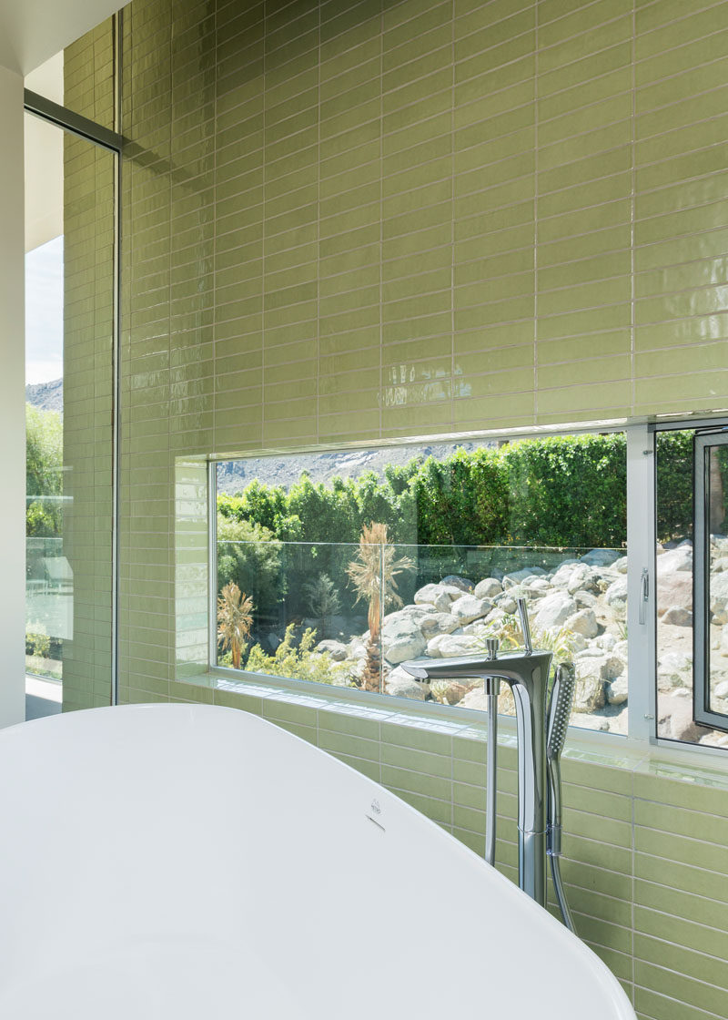 In this master bathroom, green tiles have been used to create a feature wall, and a window allows for picturesque views while having a relaxing bath.