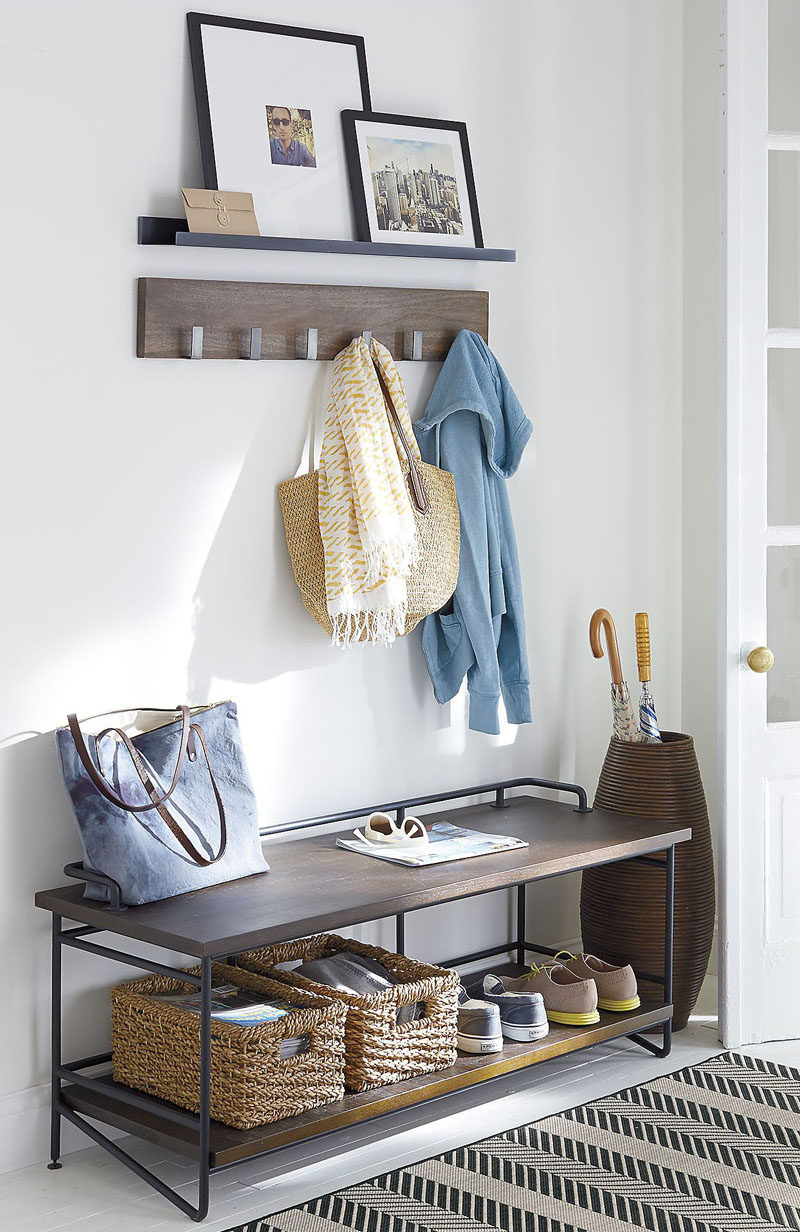 Entryway Design Ideas - 3 Different Styles Of Entryway Benches // The dark wood and metal piping on this entryway bench contrasts the white interior but matches the shelf and coat hangers above it to make the spot feel styled and put together.