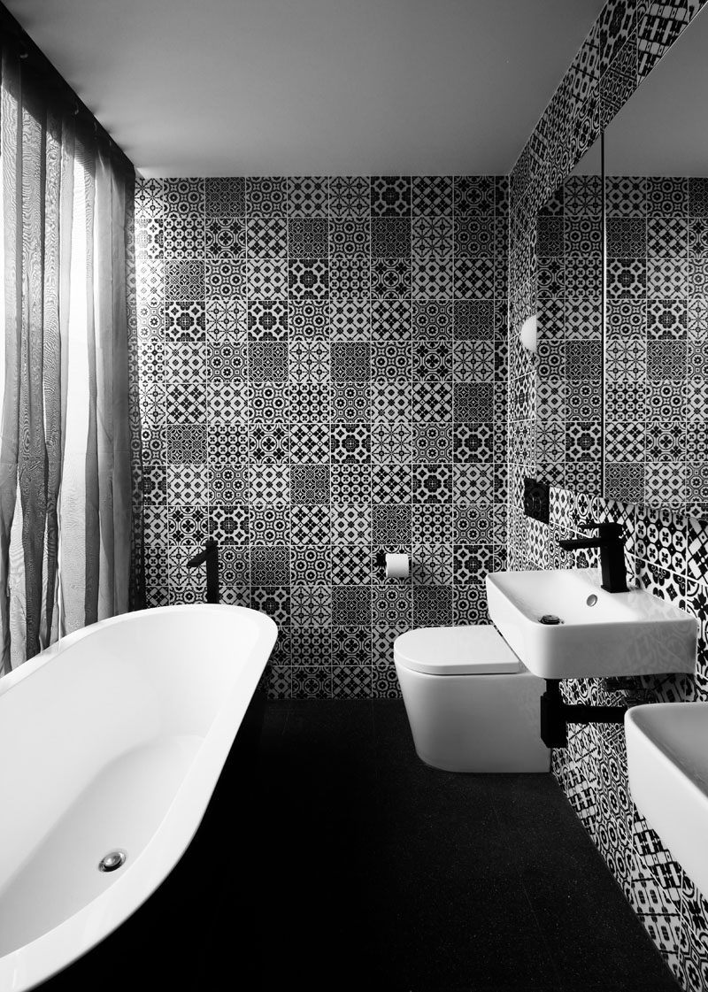 In this black and white bathroom, decorative tiles help to keep the space fun and a large mirror helps to reflect light throughout.