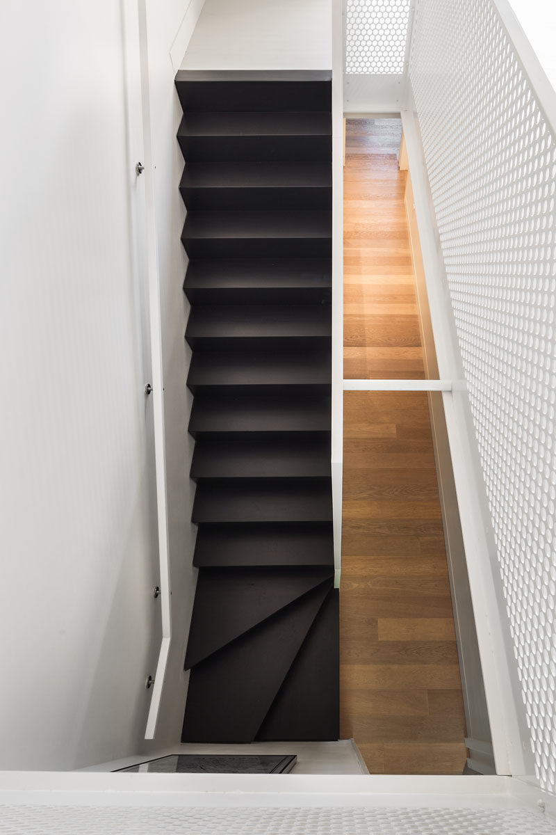 Dark stairs strongly contrast the light wood floors and white walls in this renovated home.