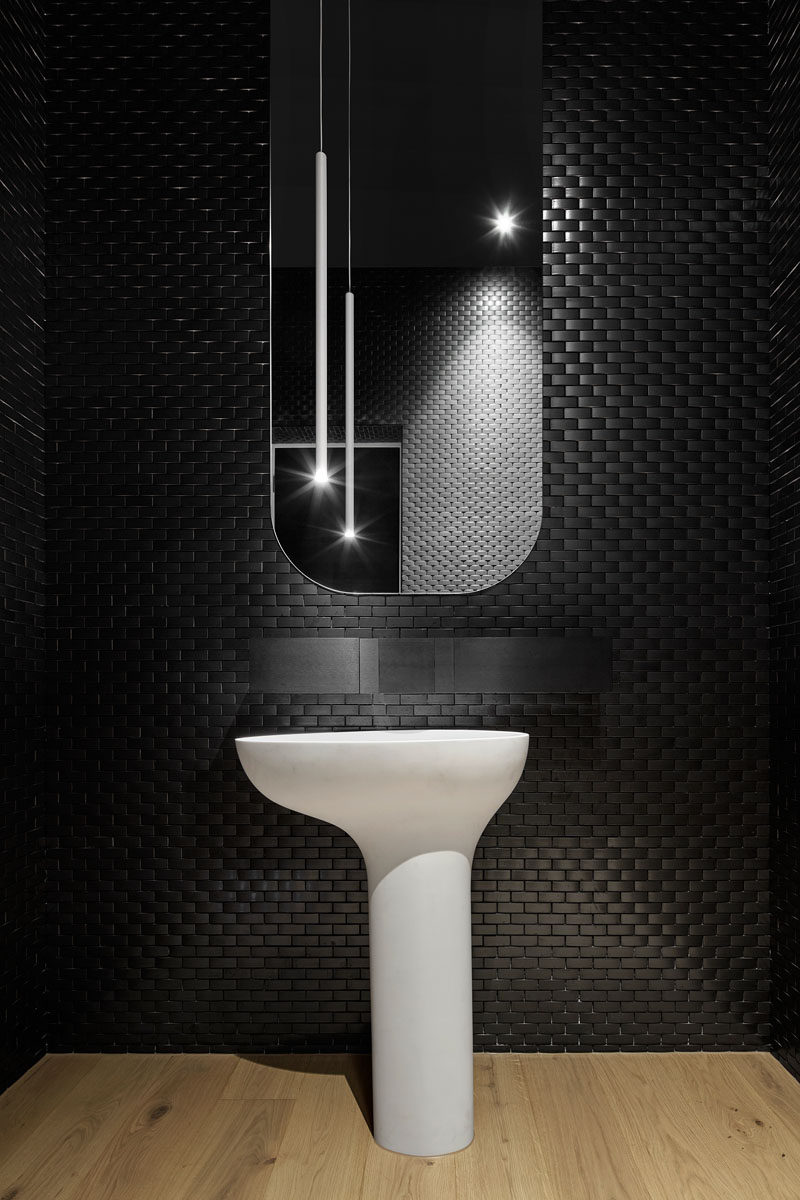 Black tiles create a bold and dramatic look in this modern powder room.