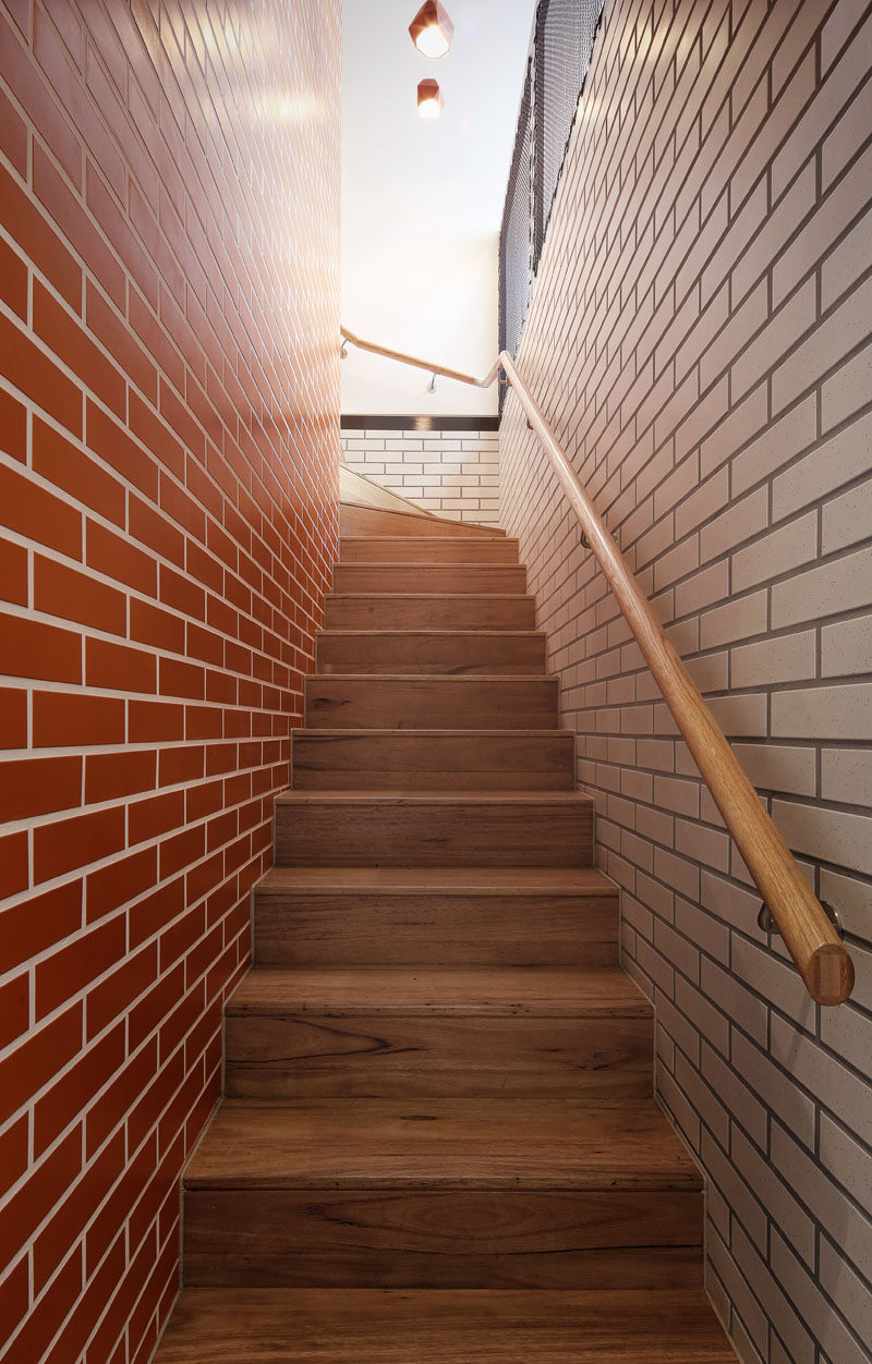 Different colored bricks line the staircase leading to the upper floor of this home.