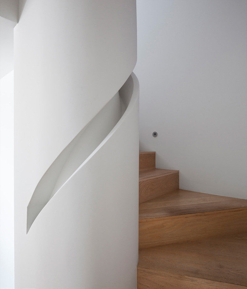 Stair Design Idea - 9 Examples Of Built-In Handrails // A custom handrail has been built into the column that this staircase wraps around.