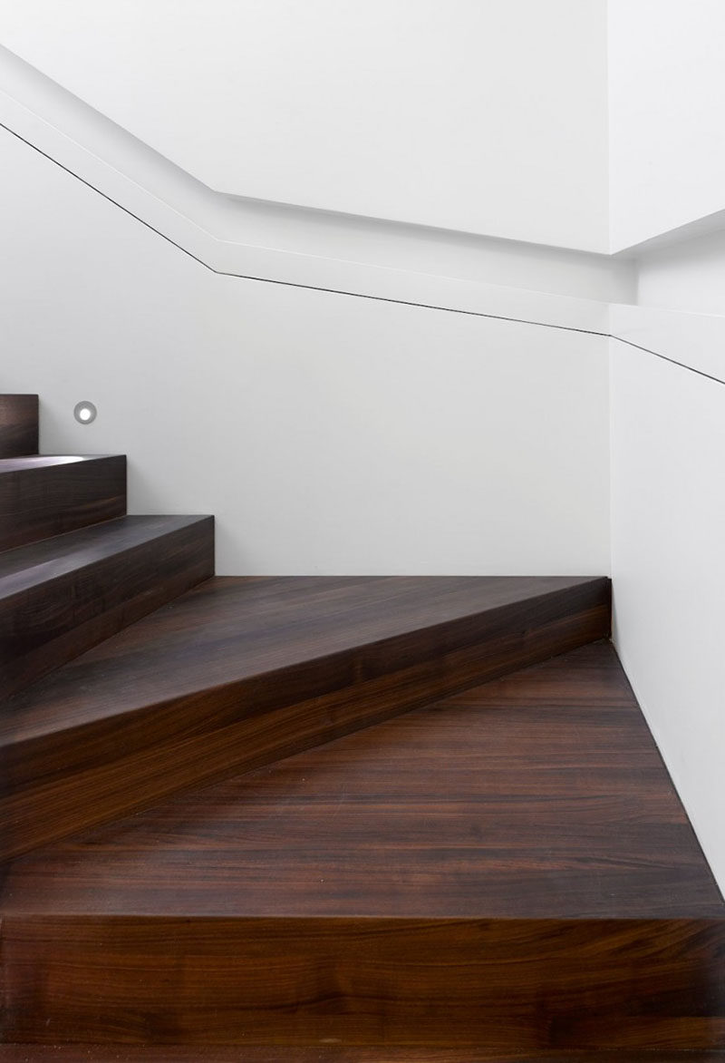 Stair Design Idea - 9 Examples Of Built-In Handrails // This white wall that wraps around the stairs has a section cut-out of it to house the handrail.