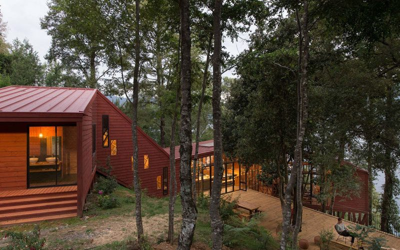 This House Is Designed With Various Levels Cascading Down A Forested Hillside