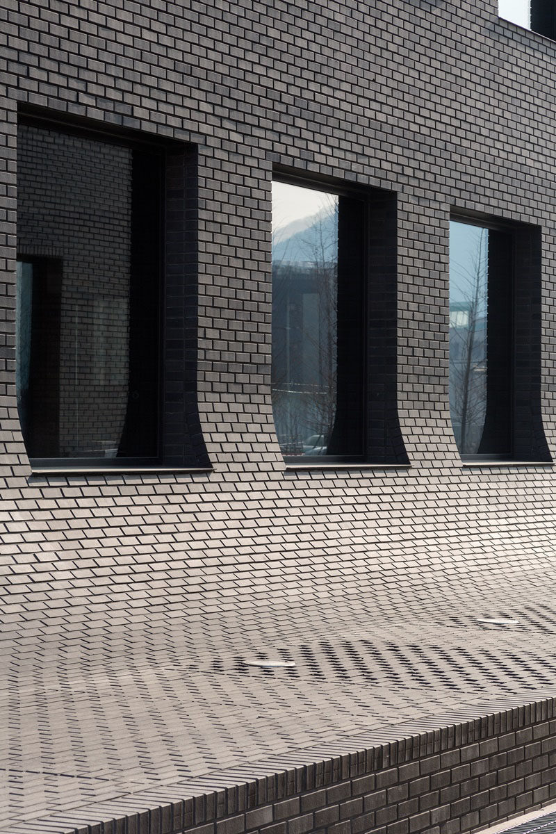This black brick building in Korea curves down to meet the sidewalk.