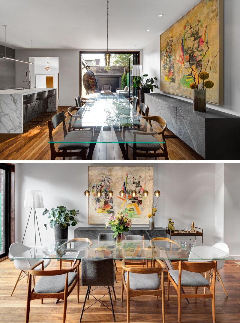 A long glass dining table is surrounded by a mixture of chairs, and a sideboard along the wall provides extra storage for serving dishes.