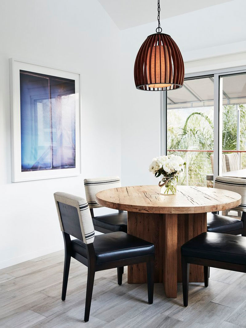 A circular wooden dining table and singular pendant light makes for an intimate dining experience.