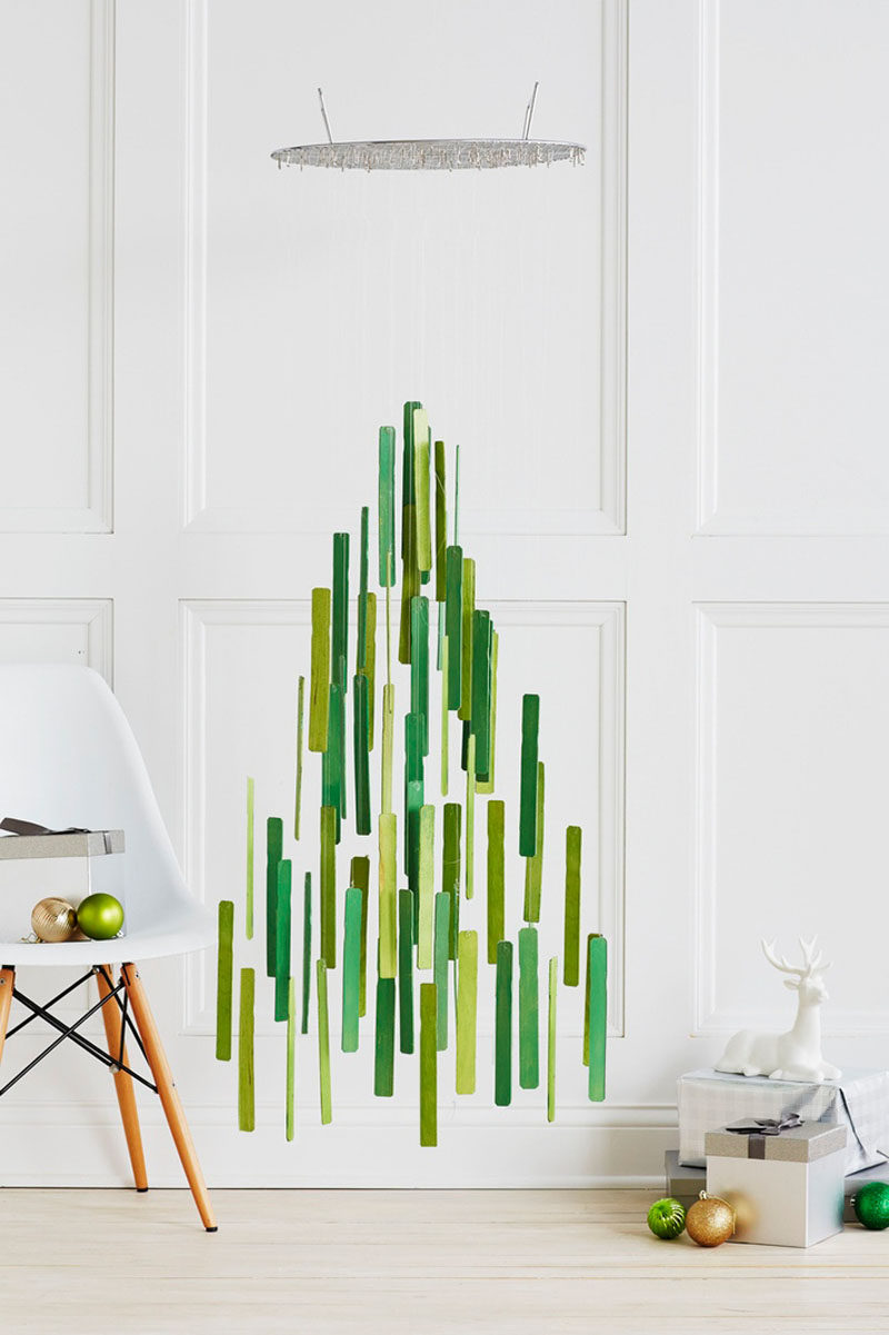 Christmas Decor Ideas - 14 DIY Alternative Modern Christmas Trees // Paint stir sticks have been painted and suspended from a steamer rack to create a floating Christmas tree alternative that has lots of room underneath it - perfect for stacking up the presents.