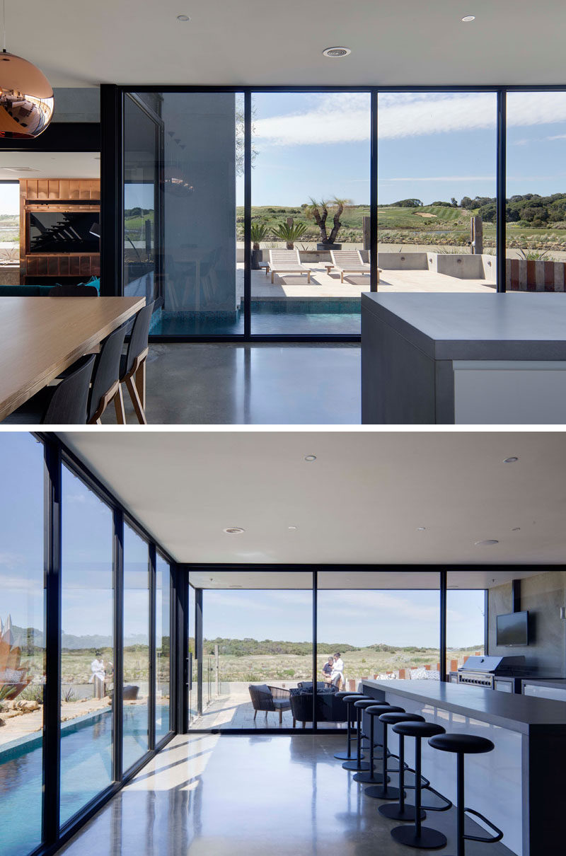 Floor-to-ceiling windows with black frames that surround the living, dining and kitchen areas provide views of the swimming pool and golf course.