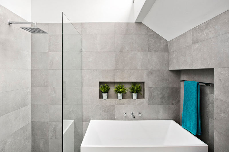This master ensuite bathroom has been kept light and airy with the use of large light gray tiles, and a white bath. A small shelf and towel rack have been included in the design of the tiled walls.