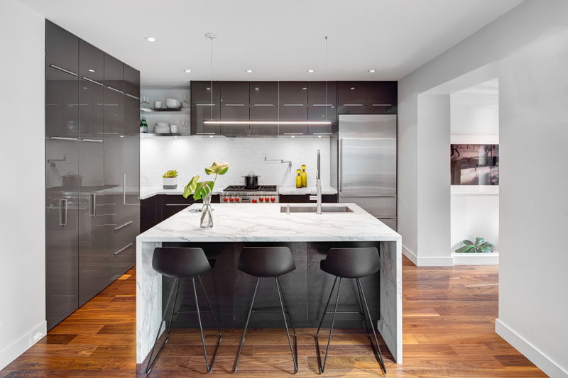 A central island, open shelves in the corner and sleek cabinetry make up this contemporary kitchen.
