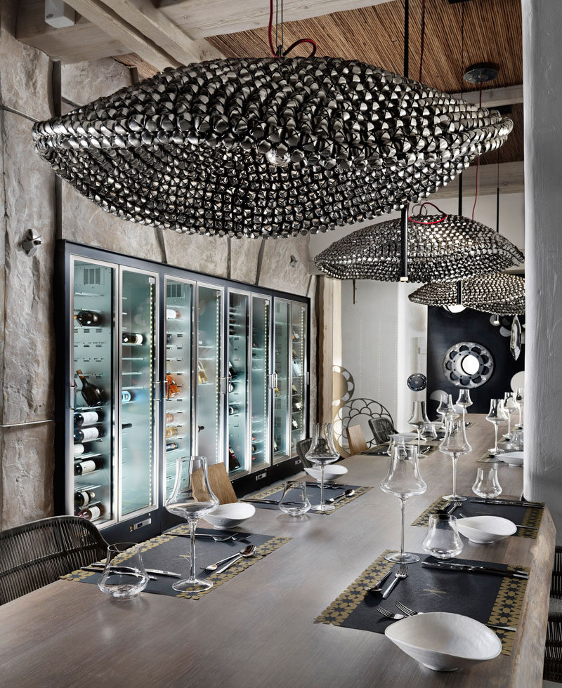 Large sculptural pendant lights hang above these restaurant tables, while a large wine fridge sits flush with the wall.