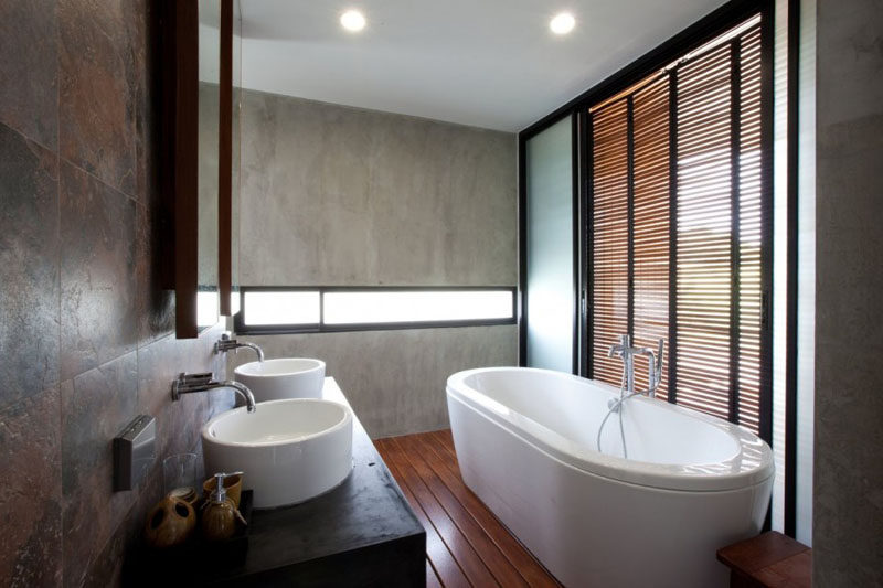 In this master bathroom, a letterbox window gives a glimpse of the outdoors and wooden shutters provide privacy but also let fresh air through.