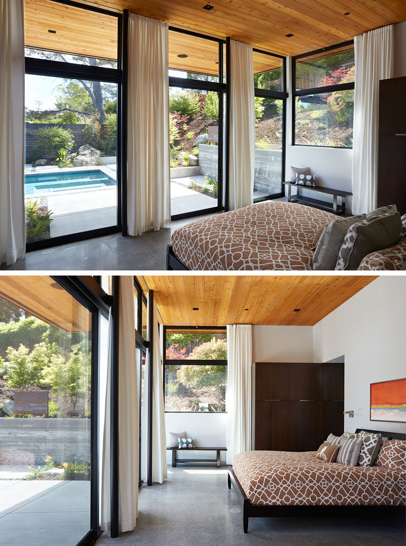 This master bedroom looks right out onto the backyard through large floor to ceiling windows and the wooden ceiling carries through too.