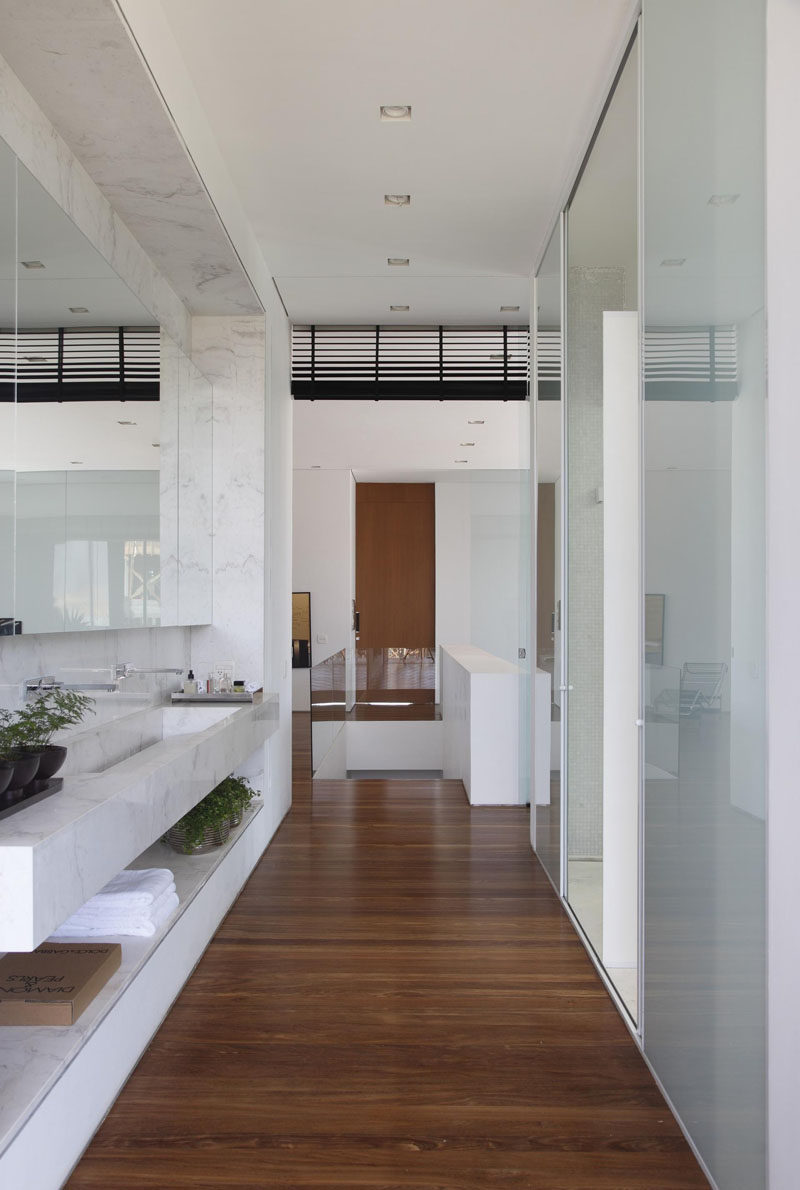In this bathroom, the color palette has been kept bright and frosted glass doors provide privacy.