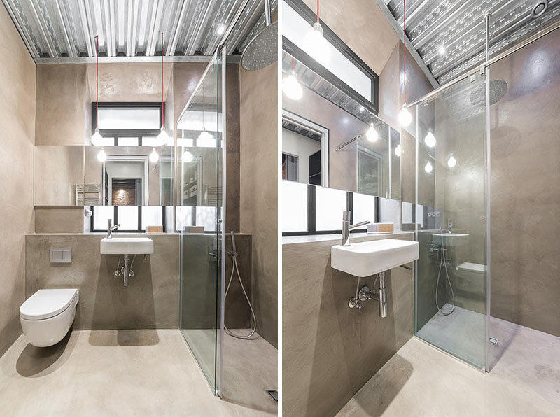 In this bathroom, a small shower is surrounded by glass helping to make the space feel larger, and the metal ceiling and large mirror aids in reflecting the light.