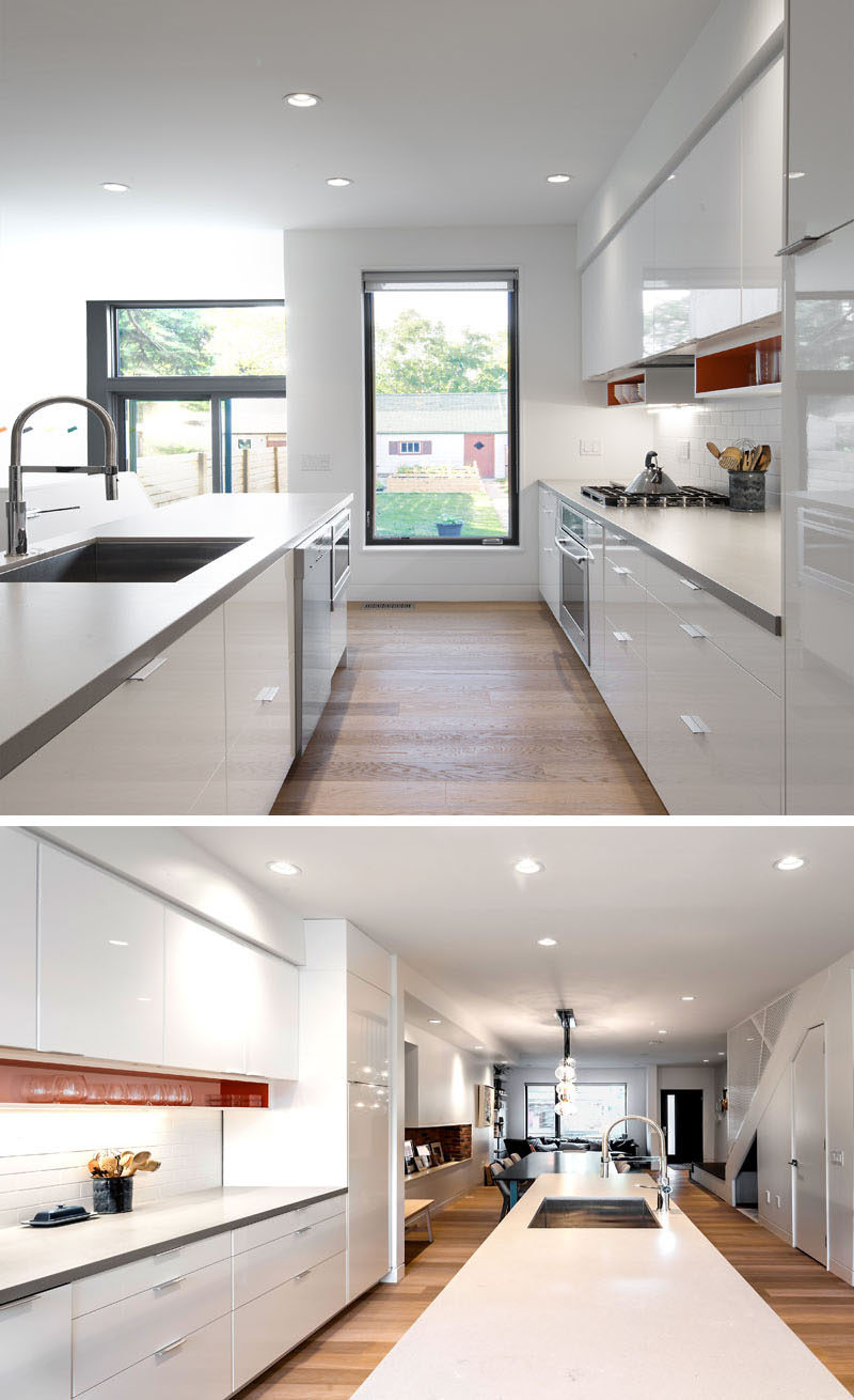 To break up this bright white kitchen, a light gray countertop and colorful shelves under the upper cabinets have been installed. A vertical window provides lots of light and views to the backyard.