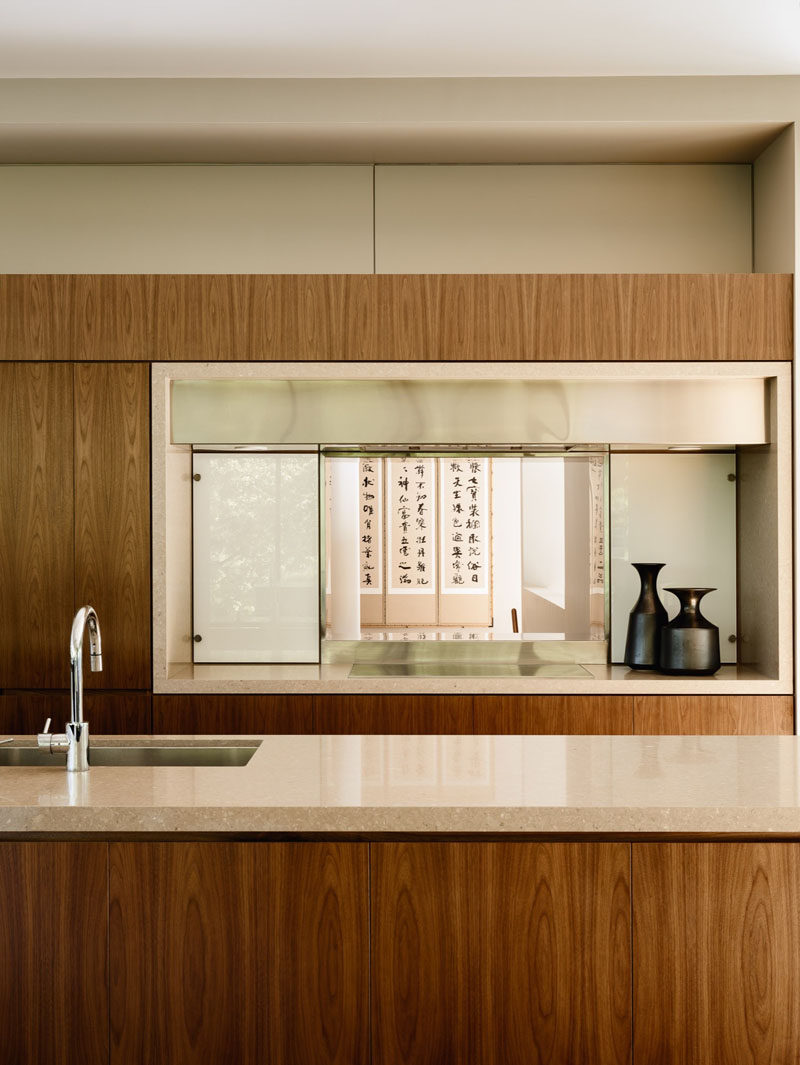 Wooden cabinetry has been paired with light cream colored stone to create a contemporary kitchen look.