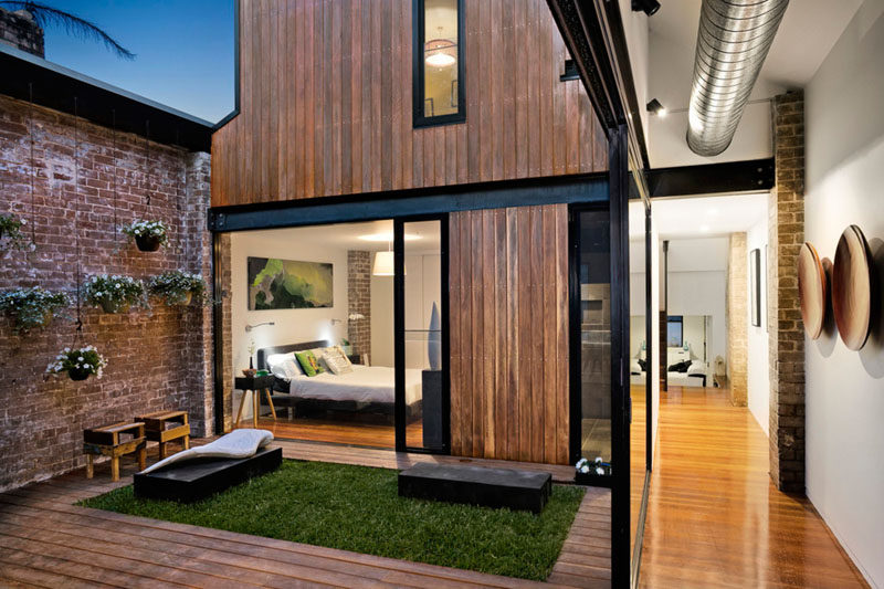 A small courtyard with a grassy patch and hanging planters separates the living area from the master bedroom in this renovated ambulance station.