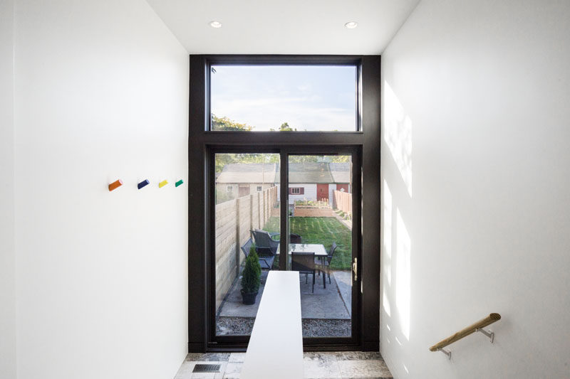 A black-framed sliding glass door provides access to the backyard and small patio in this renovated home.