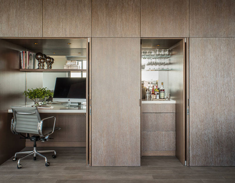 Small Apartment Design Ideas - Create A Home Office In A Closet // When the doors are closed this wall just looks like a wall of paneled wood; but upon further inspection you'll find closet doors that open up to reveal an office and bar.