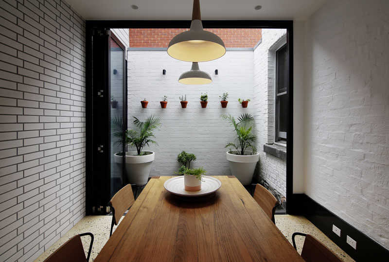 This dining room, surrounded by white bricks, opens up to a small private courtyard with wall-mounted plants.