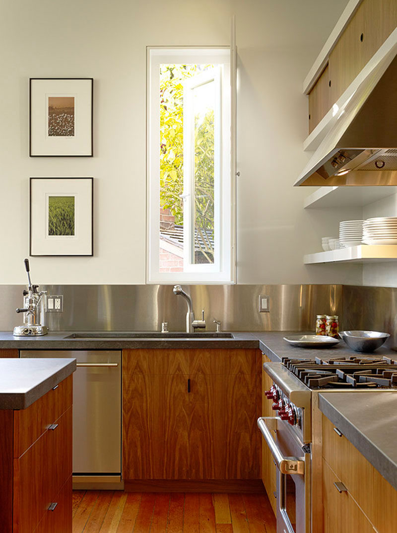 Kitchen Design Idea - Stainless Steel Backsplash // Stainless steel panels wrap around the walls of this kitchen to make for easy clean up after a messy meal.