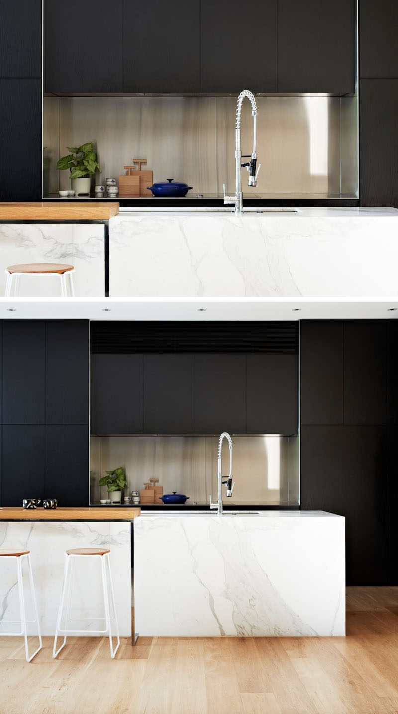 Kitchen Design Idea - Stainless Steel Backsplash // Surrounded by the black cabinets, the stainless steel backsplash in this kitchen creates a contemporary look and makes it easier to clean up when you're done cooking.