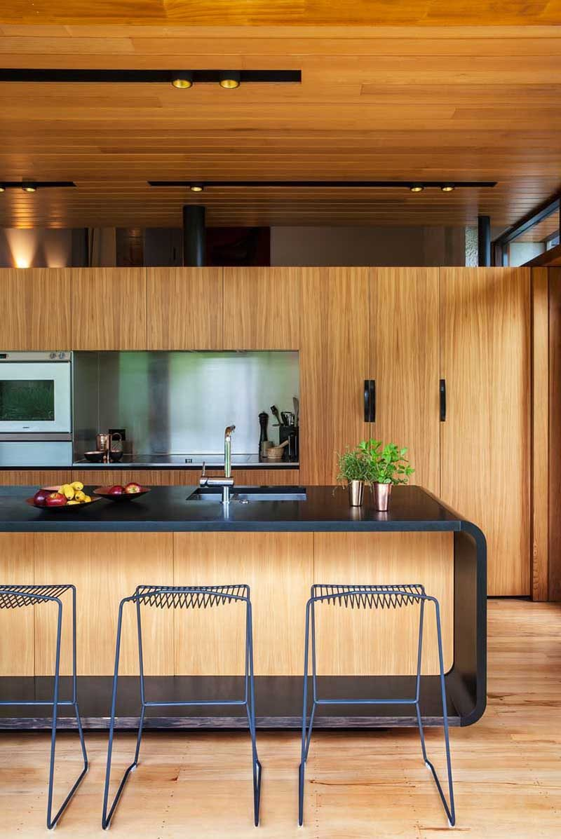 Kitchen Design Idea - Stainless Steel Backsplash // Stainless steel wraps around the cut out spaces in this kitchen to make for easy clean up and to help modernize the wood interior.