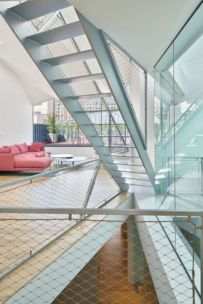 Steel stairs lead you up to the lofted bedroom and ensuite bathroom in this New York penthouse.