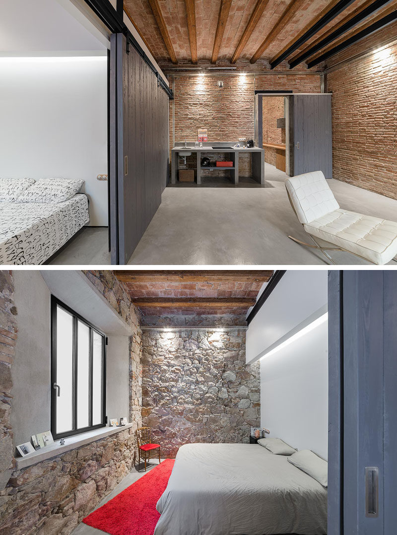In this renovated apartment, the bedroom has a pristine wall that's a strong contrast with the original stone walls.