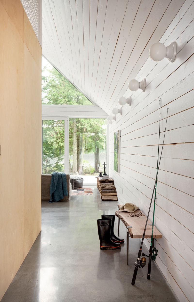 Inside this chalet, the walls are covered in white painted wood, keeping the interior bright.
