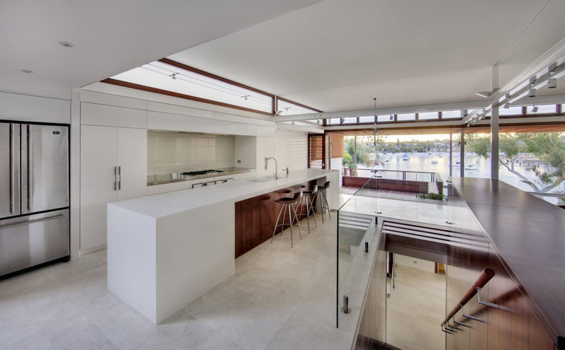 Kitchen Design Ideas - White, Modern and Minimalist Cabinets // The white cabinetry in this kitchen is warmed up with the rich toned wood along the upper windows and on the island.