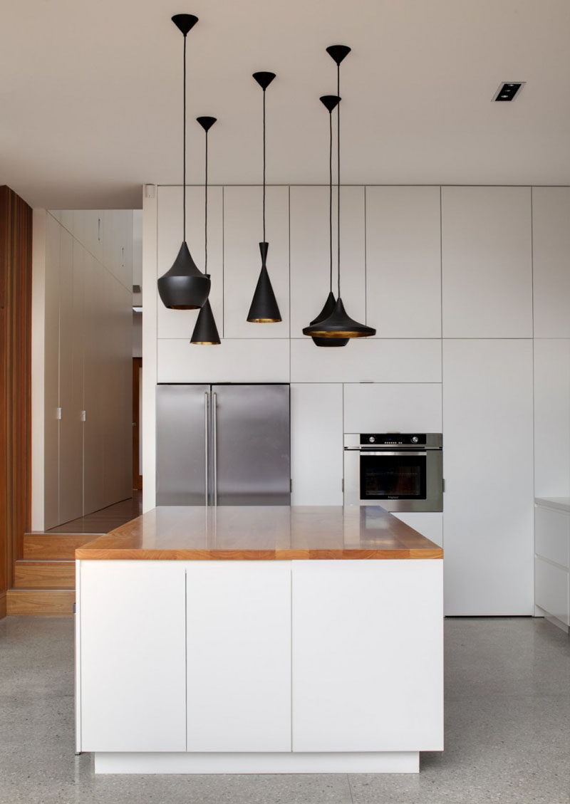 Kitchen Design Ideas - White, Modern and Minimalist Cabinets // White cabinets of different sizes give the walls a geometric look to them and the minimal hardware keeps the cupboards looking smooth.
