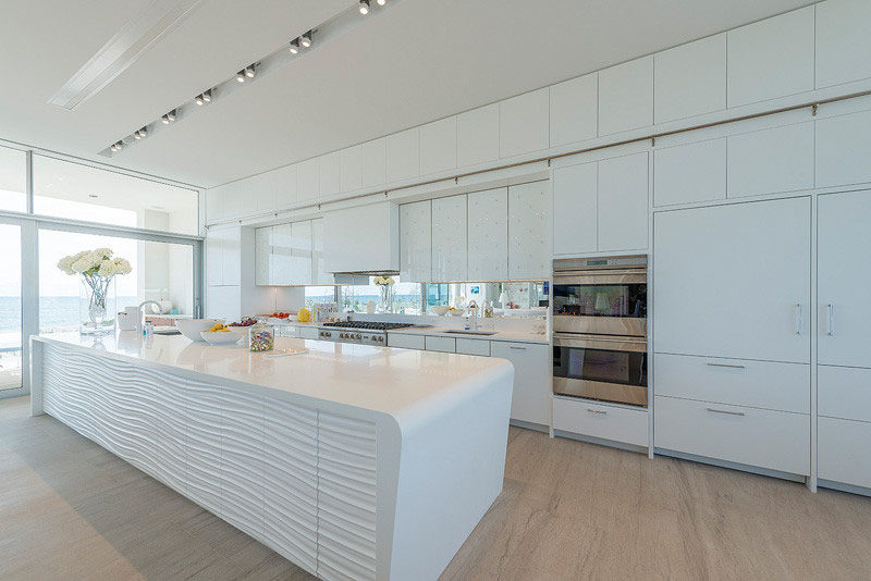 Kitchen Design Ideas - White, Modern and Minimalist Cabinets // White cabinetry, white countertops, and an all white island give this kitchen a clean look and brightens up the rest of the living space.