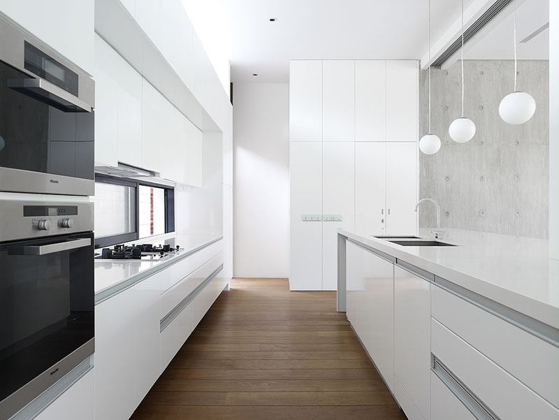 Kitchen Design Ideas - White, Modern and Minimalist Cabinets // The hardware-free white cabinets of this kitchen are softened up by warm wood flooring.