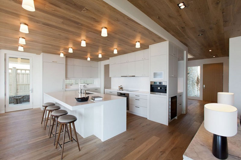 Kitchen Design Ideas - White, Modern and Minimalist Cabinets // This all white kitchen breaks up the wood floor and ceiling to create a more modern looking space.