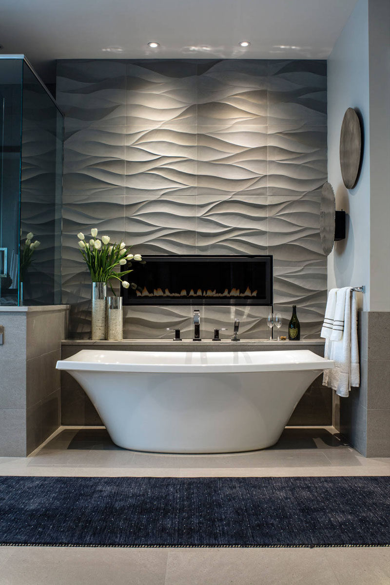 Bathroom Tile Ideas - Install 3D Tiles To Add Texture To Your Bathroom // Wavy tiles behind the bathtub and surrounding the built in fireplace create a feature wall that can also double as art.