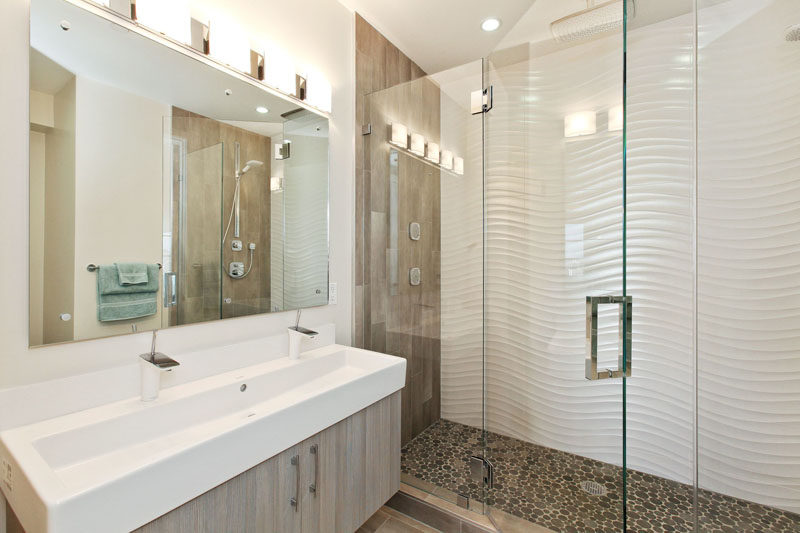 Bathroom Tile Ideas - Install 3D Tiles To Add Texture To Your Bathroom // These wavy tiles along with the pebble like shower floor and the wood details give this bathroom a modern beachy look.