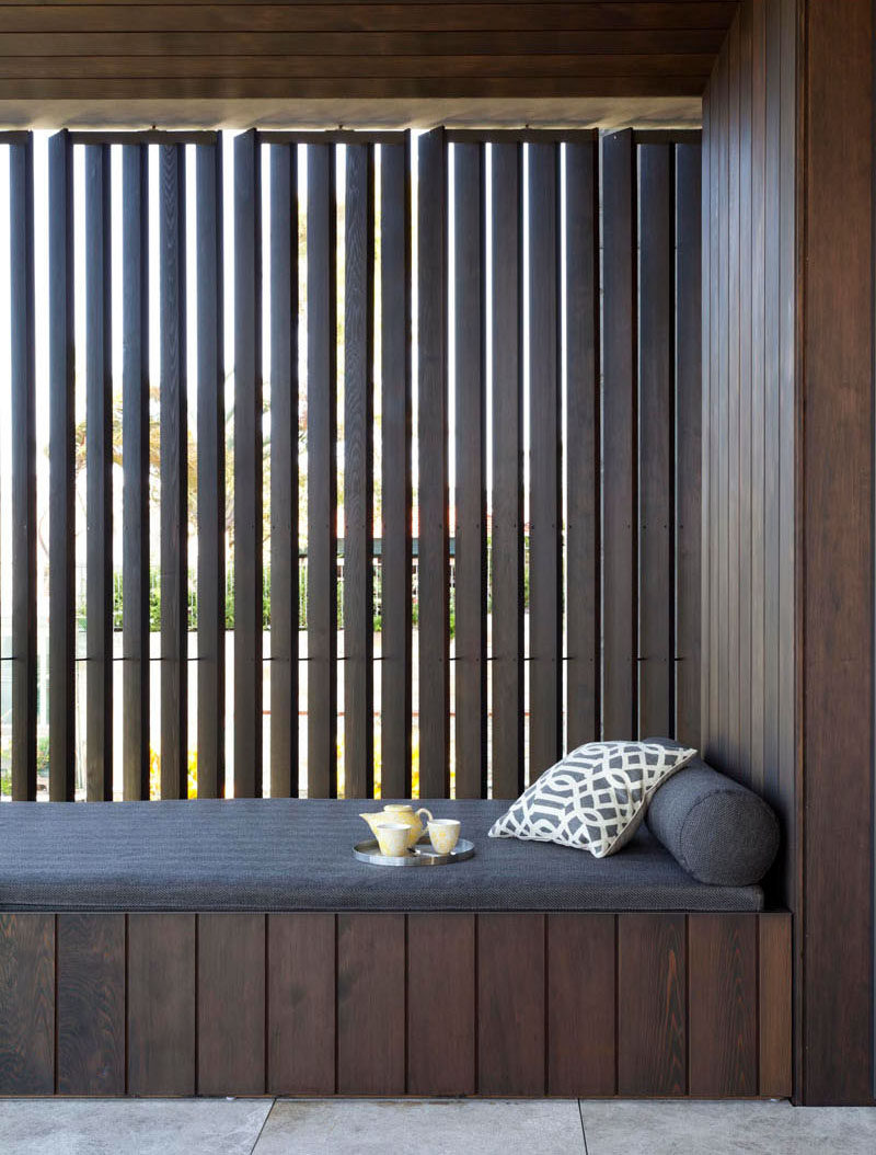 This balcony in an Australian home has a built-in daybed surrounded by dark timber.
