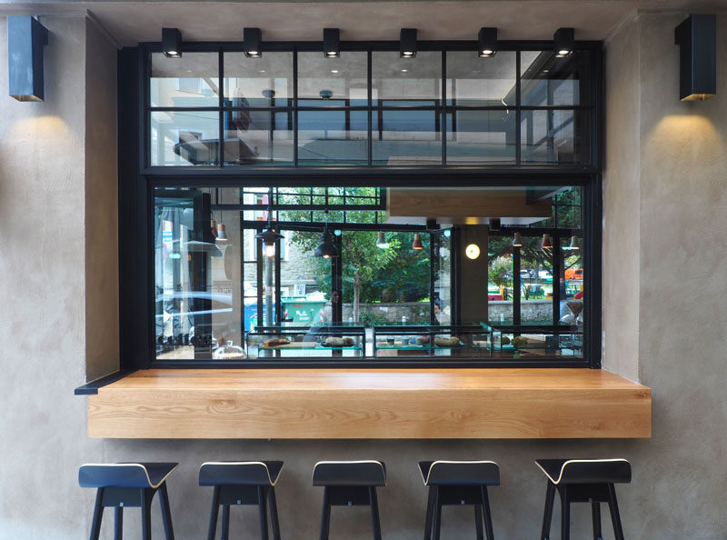 This modern cafe has a serving bar with stools that allows guests to sit outside.