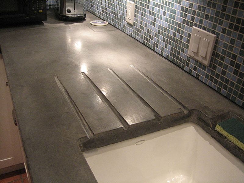 11 Creative Concrete Countertop Designs To Inspire You // This concrete countertop has been slightly angled and includes grooves to allow water to drain right into the sink without the need for a separate drainboard.
