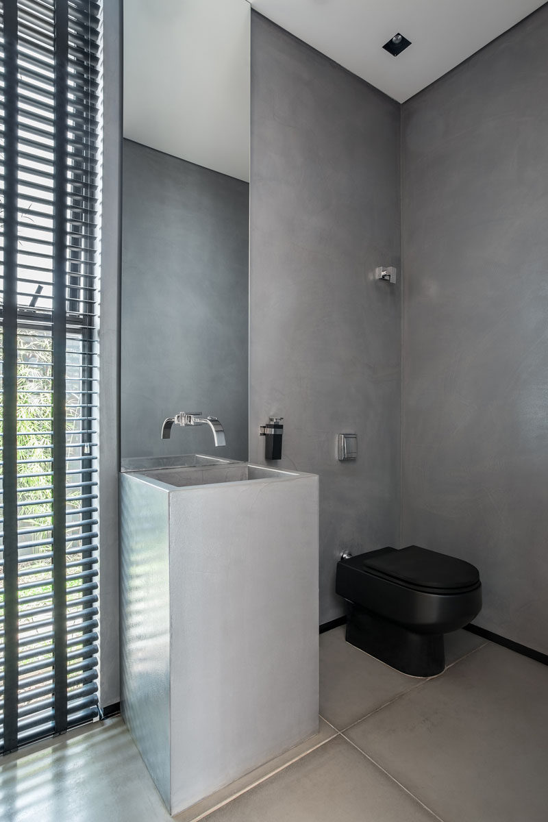 In this bathroom, there's a more masculine look with concrete walls and sink, a thin vertical mirror, and black toilet and shutters.