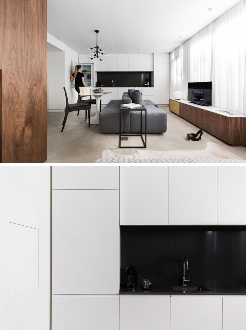 Along one wall of this small apartment is the kitchen with bright white cabinets and black backsplash. The integrated fridge gives the kitchen a seamless sleek look.