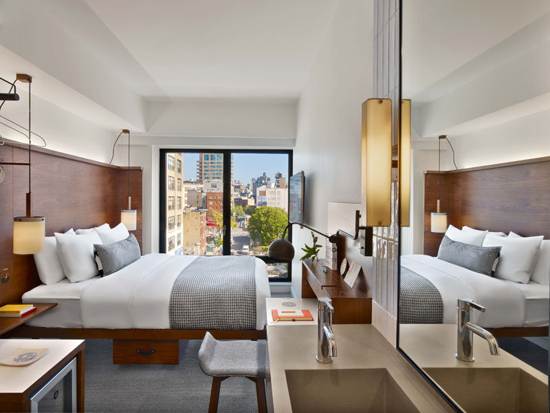 The hotel rooms at Arlo Hudson Square in NYC, have picturesque city views through a large window, and wood elements used throughout the design of the hotel make an appearance in the rooms too.