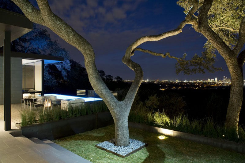 The fully landscaped yard of this house uses light to highlight the established trees and the low walls that surround the yard.