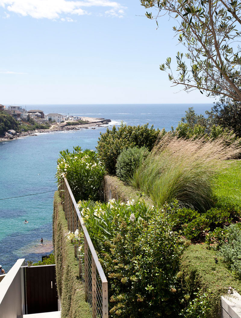 At the side of this landscaped backyard there are steps that lead down to the beach.